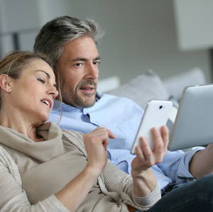 38396774 - mature couple at home using smartphone and tablet